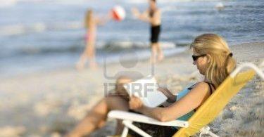 1761519-lecture-caucasienne-de-m-re-dans-la-chaise-de-salon-sur-la-plage-tandis-que-le-mari-et-la-fille-joue